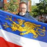 Danskeren Claus Ruhe Madsen, der her står med Rostocks flag, bliver den første udlænding, der kan sætte sig i overborgmesterstolen i en tysk storby. Ruhe Madsen stillede op som uafhængig i Rostock og blev støttet af kristendemokraterne, CDU, og det liberale FDP. I bystyret er der imidlertid et andet flertal Her skal Ruhe Madsen arbejde sammen med et flertal bestående af Die Linke, SPD og De Grønne.