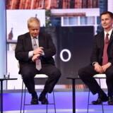 Her er de to mænd, som skal kæmpe om at blive briternes næste premierministre. Billedet er fra den modløse TV-debat tirsdag aften, og det fanger dem ikke i det mest inspirerende øjeblik – til venstre tidligere udenrigsminister Boris Johnson, som kigger på uret og sikkert håber, at debatten snart er forbi, og til højre nuværende udenrigsminister Jeremy Hunt, som ikke ser mere interesseret ud.