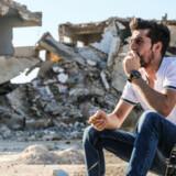 Mohammed Kabbani ryger en cigaret foran ruinerne i sin hjemby, Binnish, i Syriens Idlib-provins. Han kom frivilligt tilbage hertil, selv om han havde asyl i Europa. Nu kan han ikke rejse ud igen.