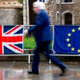 (FILES) In this file photo taken on March 18, 2019 A pedestrian walks past the Union (L) and EU flags of anti-Brexit activists near the Houses of Parliament in London on March 18, 2019. - Britain will slide into a year-long recession should it leave the European Union without a deal with Brussels, the government's official forecaster said on July 18, 2019. (Photo by Niklas HALLE'N / AFP)