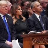 Præsident Donald Trump og tidligere præsident Barack Obama – her med USAs førstedame, Melania Trump, imellem – holdt takt og tone og facaden udadtil under statsbegravelsen af tidligere præsident George H.W. Bush i december sidste år. Men deres konflikter er dybe. Til højre tidligere førstedame Michelle Obama.