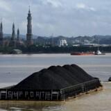 En flodpram med kul på vej til et af Indonesiens stigende antal kulkraftværker. FN advarer nu om, at de fortsatte investeringer i nye kulkraftværker i Asien risikerer at bringe Parisaftalens temperaturmål i fare.
