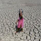 Hyppigere og kraftigere hedebølger og generelt mere voldsomt vejr påvirker mennesker verden over. Her ses en kvinde på en udtørret sø i Indien. (ARKIV).