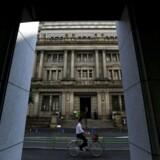 En man cykler foran Bank of Japans bygning i Tokyo.