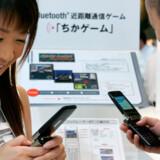 To besøgende spiller videospil på mobiltelefonen ved Tokyo Game Show.