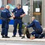 Den formodede gerningsmand ligger på jorden, efter at politiet har skudt ham i benet i forbindelse med anholdelsen. Foto: Kirsi Kanerva