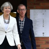 Premierminister Theresa May har stemt på sit valgsted i Maidenhead. Bagved står hendes mand Philip. Scanpix/Ben Stansall