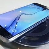 Galaxy S6 Edge, som her ses udstillet fastlænket til en holder på sidste uges Mobile World Congress i Barcelona, har også skærm på kanten, hvor man kan se korte beskeder, og så er den tidligere plastikramme nu udskiftet med metal, så designet virker lækrere. Galaxy S6 Edge og Galaxy S6 er Samsungs nye toptelefoner, der kommer i handelen i Danmark 11. april. Foto: EPA/Yonhap/Scanpix