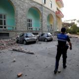 En politimand går forbi to beskadigede biler og en delvist ødelagt bygning i hovedstaden Tirana, der lørdag eftermiddag blev ramt af et jordskælv. Florion Goga/Reuters