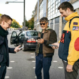 Onsdag morgen ved indgangen til Parken efter et kapløb gennem byen. Fra venstre står journalisterne Jonas Stenbæk (metro), Jens Ejsing (bil) og Frederik Volstrup (cykel) og sammenligner rejsetider.