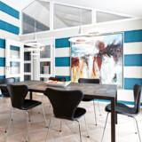 Væggene ved spisepladsen i køkken-alrummet er beklædt med tapet fra Harlequin i brede, vandrette hvide og blå striber. Bordet fra Rübner er beklædt med genbrugsskifer fra taget af Odd Fellow Palæet, da det blev renoveret. Maleriet er af den lokale Lejre-kunstnergruppe Abstra.