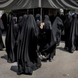 Et billeder af Iranske øverste leder Ali Khamenei vises mens en kvinde forlader fredagsbønnen i Teheran.
