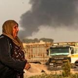 En kurdisk kvinde ser til, mens røgen stiger til vejrs fra tyrkiske bombardementer inde i det kurdiske område i Syrien.