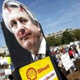 Unge demonstranter bærer et skilt med et billede af Shells topchef, Ben van Beurden. Nu tager han til genmæle mod kritikken af olieselskaberne. Foto: Samuel Corum/AFP/Ritzau Scanpix