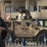 En soldat fra kurdiske ser på, mens et amerikansk militærkøretøj forlader basen i den nordsyriske by Tal Tamr.