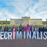 Medlemmer af Amnesty International i Nordirland demonstrerede ude foran Nordirlands lovgivende forsamling med skiltene afkriminnaliseret. Simon Graham/Reuters