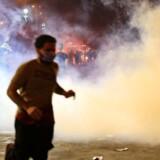 En demonstrant løber fra tåregas under protesterne mod Iraks regering i den shiamuslimske by Kerbala i Irak, syd for Baghdad. Søndag gik demonstranterne til angreb mod Irans konsulat i byen.