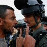 En palæstinensisk demonstrant diskuterer med en israelsk grænsevagt under en demonstration mod de israelske bosættelser på den besatte Vestbred i sidste uge. Nu ændrer USA kurs og meddeler, at man ikke betragter de omstridte bosættelser som værende i strid med folkeretten - et synspunkt, der ikke deles af langt størstedelen af FN's medlemslande. Hazem Bader/Ritzau Scanpix