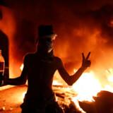 En ung irakisk demonstrant poserer foran det brændende iranske konsulat i Najaf.