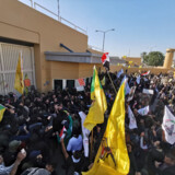 Protesters and militia fighters gather to condemn air strikes on bases belonging to Hashd al-Shaabi (paramilitary forces), outside the main gate of the U.S. Embassy in Baghdad.