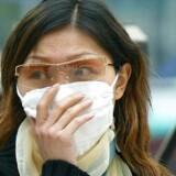 En kvinde dækker sit ansigt til under SARS-epidemien i den sydlige storby Guangzhou i 2004. Arkivfoto: Liu Jin