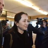Meng Wanzhou, som både er Huaweis koncernfinansdirektør og datter af Huaweis stifter, forlader sammen med sine sikkerhedsvagter højesteretsbygningen i Vancouver efter den første retsdag om hendes udlevering til USA.
