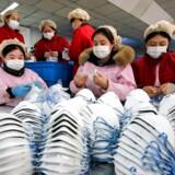 Arbejdere fremstiller masker i Handan i Kinas nordlige Hebei-provins. Kina har forbudt togafgange og flyvninger fra storbyen Wuhan, som er centrum for et farligt virusudbrud. Det vil tage mindst et år at udvikle en vaccine, siger forskere.