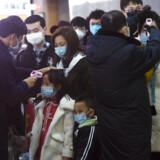 Kropstemperaturer bliver tjekket hos passagerer, der ankommer med tog til den østkinesiske by Hangzhou fra Wuhan.