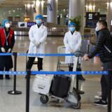 Medicinsk personale holder øje med passagerer i lufthavnen i Changsha, Hunan-provinsen i Kina. Luftfartsaktier er nogle af dem, der er blevet hårdest ramt, af frygt for at coronavirussen vil bremse rejseaktiviteten.