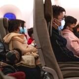 Der er næppe grund til at bære mundbind på flyrejsen – som på dette fly fra Melbourne til Shanghai 4. februar. Men en maske signalerer hensynsfuldhed og forhindrer dig i at røre mund og næse med potentielt inficerede fingre.