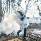 TOPSHOT - A migrant throws a gas canister back to Greek police on the buffer zone Turkey-Greece border, at Pazarkule, in Edirne district, on February 29, 2020. - Thousands of migrants stuck on the Turkey-Greece border clashed with Greek police on February 29, 2020, according to an AFP photographer at the scene. Greek police fired tear gas at migrants who have amassed at a border crossing in the western Turkish province of Edirne, some of whom responded by hurling stones at the officers. The clashes come as Greece bolsters its border after Ankara said it would no longer prevent refugees from crossing into Europe following the death of 33 Turkish troops in northern Syria. (Photo by BULENT KILIC / AFP)