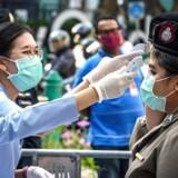Sundhedsmedarbejdere tjekker kropstemperaturen på politifolk før en demonstration i Bangkok. Overalt i verden er der voldsomt skærpet fokus på at inddæmme spredningen af ny coronavirus.