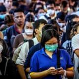 Hele verden er grebet af frygt for den nye feber. Her pendlere, der venter på en kanalfærge i Bangkok 2. marts i år.
