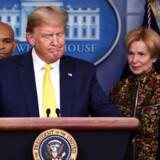 Præsident Donald Trump gestikulerer, mens han under en pressebriefing i Det Hvide Hus taler om coronavirus med vicepræsident Mike Pence og andre fra indsatsstyrken mod coronavirus omkring sig.