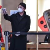 En sikkerhedsvagt med mundmaske på kontrollerer kundernes temperatur, før de får lov til at komme ind i Apples butik i Shanghai. Coronavirussens hærgen har ramt Apple hårdt på flere områder.