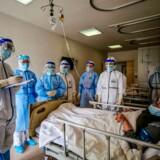 Sundhedsperonale taler med en patient, der er indlagt på hospital i den kinesiske by Wuhan med den nye sygdom covid-19.