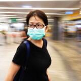 Kvinde ses med ansigtsmaske i metrostationen Orchard Road i Singapore torsdag. Bryder man karantænen i Singapore, kan man få bøder på op til 66.000 kroner – eller et halvt års fængsel.
