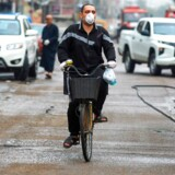 An Iraqi man, wearing a protective mask, rides a bicycle down street in the capital Baghdad on March 16, 2020 amidst efforts against the spread of COVID-19 coronavirus disease. (Photo by AFP)