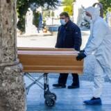 En bedemand i beskyttelsesudstyr ruller en kiste med en død patient bort i Bergamo i den italienske provins Lombardiet. Gennemsnitsalderen for det stigende antal døde af covid-19 i Italien er 81 år, og ca. 80 procent er mænd.