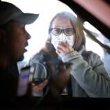 Israels regering åbner for overvågning af mobiltelefoner for at begrænse coronasmitte. Her ses en hospitalsmedarbejder tale med en borger, der skal testes for corona i Maryland, USA. Chip Somodevilla/Getty Images/AFP