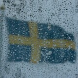 The Swedish flag is seen through a snow-covered window at the Alpine Skiing World Championships 2007 in Are, Sweden February 4, 2007. The women/s super-G competition scheduled for Sunday has been postponed until Tuesday because of bad weather, organisers said. REUTERS/Pascal Lauener (SWEDEN)