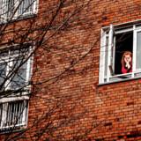 Anne Kristine Brix Poulsen arbejder hjemme på grund af corona. Og hun keder sig. Her ses hun i sit vindue på Vesterbro i København.