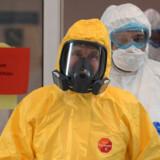 Iført gul beskyttelsesdragt var Ruslands præsident, Vladimir Putin, tirsdag på besøg på et hospital for coronasmittede. Nu tvinger epidemien ham til at udskyde en planlagt folkeafstemning, der kan resultere i, at han kan bliver på posten helt frem til 2036. Alexey Druzhinin/Ritzau Scanpix
