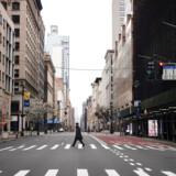 En mand krydser en mennesketom gade på Manhattan i New York City, der er blevet epicenter for det hastigt voksende udbrud af coronavirus i USA. Billede er fra 25. marts.