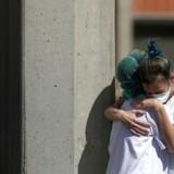 Sygepersonale krammer hinanden uden for en intensivafdeling ved Severo Ochoa Hospital i Spanien.
