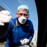 Når man tester for virus på personer med lette symptomer, foretager man typisk en podning af halsen eller svælget. Test for immunitet sker med en blodprøve, som har færre fejlresultater. På billedet foretager en tysk læge en test for virus gennem et åbent bilvindue.