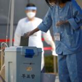 Midt i coronakrisen er der parlamentsvalg på onsdag i Sydkorea. Her afgiver en covid-19-patient sin stemme forud for valget.