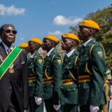 """(FILES) This file photo taken on August 14, 2017 shows Zimbabwe President Robert Mugabe (2L) inspecting a guard of honour during official Heroes Day commemorations held at National Heroes Acre in Zimbabwe. Zimbabwe's military appeared to be in control of the country on November 15, 2017 as generals denied staging a coup but used state television to vow to target """"criminals"""" close to President Robert Mugabe. / AFP PHOTO / Jekesai NJIKIZANA"""