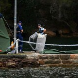 En betjent bærer vragdele fra flyet, der styrtede i en flod nær Sydney nytårsaftensdag. Ombord var seks personer, herunder mangemillionæren Richard Cousins. Alle, der var ombord på flyet, døde i styrtet.