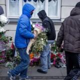 Unge mænd fjerner blomsterne på stedet hvor den formodede drabsmand selv blev skudt og dræbt.